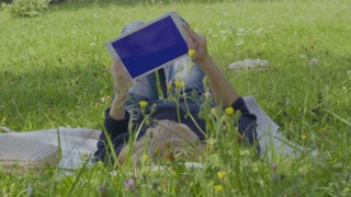 Young woman uses digital tablet relaxing on blanket in park