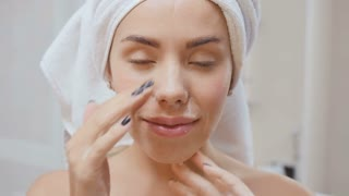 Young woman washes face with gel for facial washing in slowmotion