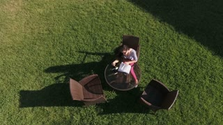 Young woman with flower sits in wicker armchair at green lawn and read book