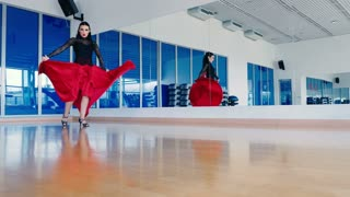 Young woman with red lips dancing tango in gym