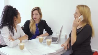 Young women talking with boss on phone sitting at lunch break in cafe