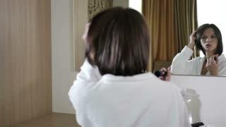Woman adjusts makeup in the mirror in the bedroom