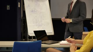 Woman makes notes about a presentation