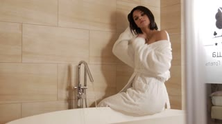 Woman sitting on the bathtub in the bathroom