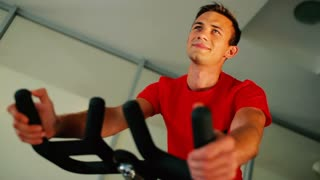 Young attractive man cycling on the exercise bike in the gym
