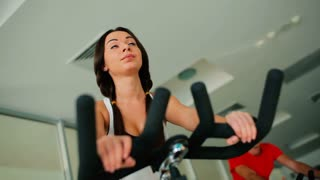 Young beautiful woman cycling on the exercise bike in the gym