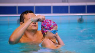 Young father corrects the goggles on head of little girl in the swimming pool