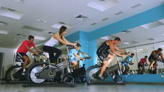 Young sports people training with coach on the exercise bike in the gym