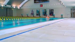 Young sports woman swimming crawl in the swimming pool