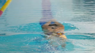 Young sportsman training to swim butterfly in the blue swimming pool