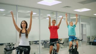 Young sportsmen are training breathing exercise on the exercise bike in the gym