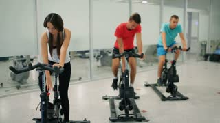 Young sportswoman and men is training on the exercise bike in the gym