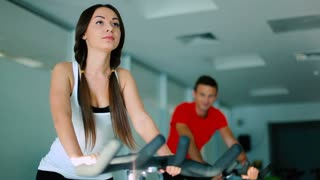Young woman with long hair training on the exercise bike in the gym