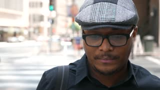 African American businessman smiles into camera downtown.