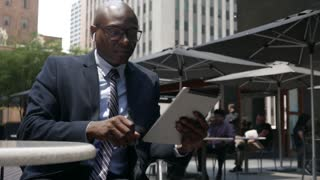 African American businessman works on iPad and iPhone in outdoor cafe - tech!