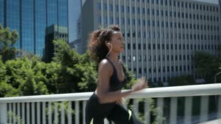 African American woman runs full speed across a bridge.  Dynamic shot.