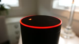 Amazon Alexa (Echo) lights up as it is voice-activated in a bedroom (darker background).