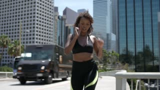 Beautiful African American woman catches her breath after a run downtown.