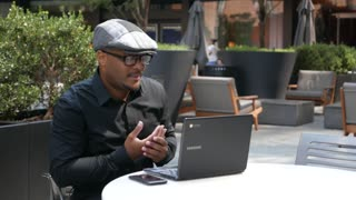 Businessman in outdoor cafe works on laptop and drinks water.