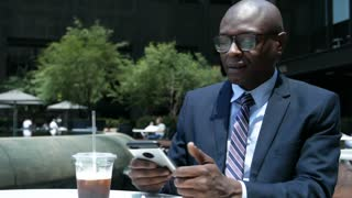 Businessman on his Phone while drinking Iced Coffee and listening to Earbuds