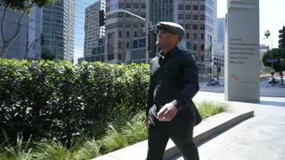Businessman walks through downtown and talks on phone.  New Yorker in LA.