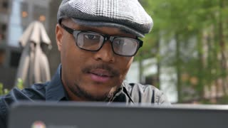 Businessman with glasses works on laptop at an outdoor cafe