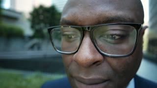 Extreme closeup of glasses on a businessman's face.