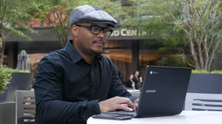 Hip businessman works on laptop in outdoor cafe.