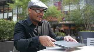 Internet Startup businessman with glasses works on laptop at outdoor cafe.