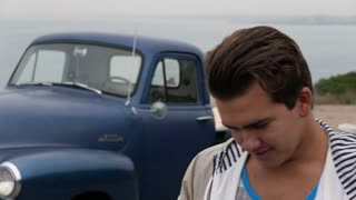 Millennial smiles into camera with classic 1950s truck behind him.
