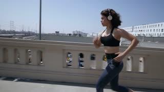 Profile running shot of woman running through a city.  Train tracks below.