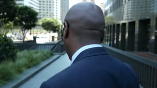 Reverse of businessman as he walks through downtown.