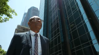 Titan of industry businessman strolls through downtown - dramatic shot.