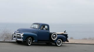 Young adult exits his 1950s Chevy truck to grab his surfboard for the beach.