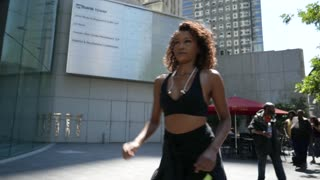 Young African American Woman power walks by a building downtown