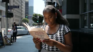 Young African American woman reads a book while walking downtown
