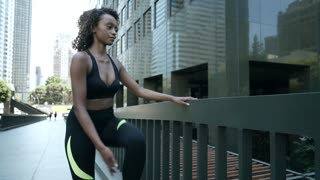 Young African american woman stretches before a run downtown.