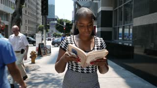 Young African Americans woman reads a book while walking