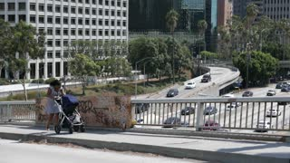 Young businesswoman and mother pushes a stroller through dirty part of the city.