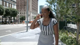 Young businesswoman making deals on her phone while walking to work.