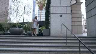 Young businesswoman walks down stairs in a city.