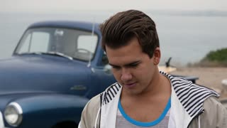 Young man looks into camera with a 1950s Chevy truck and beach in the background