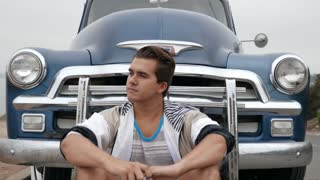 Young man sitting in front of grill of 1950s Chevy truck, smiles into lens.