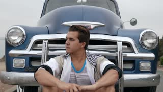 Young man sitting in front of grill of 1950s Chevy truck.