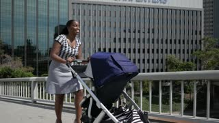 Young Mom pushes stroller through the city on her way to work.