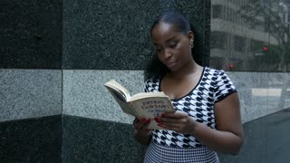 Young woman reads a book in a downtown city.