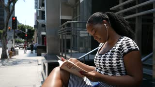 Young woman reads a book outside while on a lunch break from work.