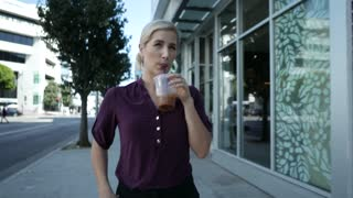 Young woman walks downtown with an iced coffee in hand.