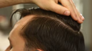 Barber master smoothing and combing hair of client