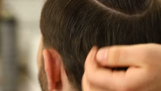 Barber smoothing hair of client
